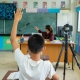 child raising hand in classroom set up for hybrid learning due to pandemic